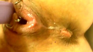 Pierced pussy masturbated by a small purple vibrator at home