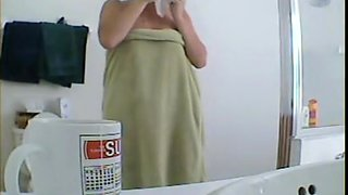 Girl in the shower oiling nude tits and getting dressed
