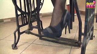 Pretty chick wearing high heels Petra sews on the sewing machine