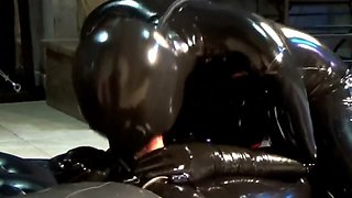 couple in black latex catsuit mask and the blowjob girl