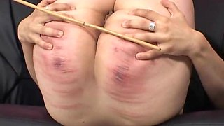 Horny girl moans loudly while a mistress hits her with a stick