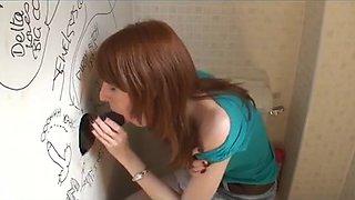 Pale freckled redhead sucks through a gloryhole