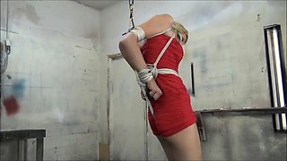 Girl in red dress and heels strappado with crotch rope
