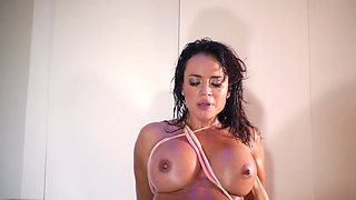 A hot Latina places oil over her sexy and busty body before fucking