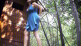 Woman in blue dress pissing next to wood shelter
