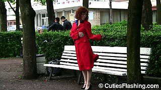Pale skin redhead babe in red raincoat flashes her body nude in public place
