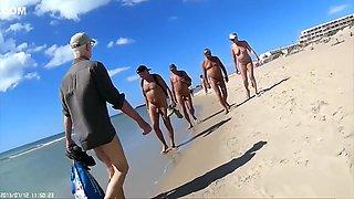 Group of mature nudists walks around the beach naked
