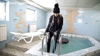 wetlook girl with winter clothes swims in the pool